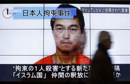 Man walks past screens displaying TV news program showing image of Goto, one of two Japanese citizens taken captive by Islamic State militants, on a street in Tokyo