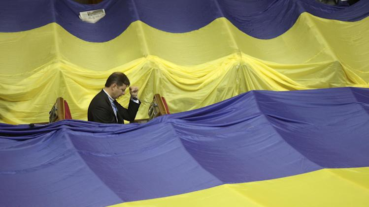 A lawmaker sits in the Ukrainian parliament after a vote of the bill of language, during a session in Kiev, Ukraine, Tuesday, June 5, 2012.  A large Ukrainian flag covered the seats of oppositions lawmakers.  Several thousand flag-waving activists staged a noisy protest outside the parliament building, protesting the bill that would keep Ukrainian as the only official language in the country, but Russian could be used in courts, hospitals and other institutions in Russian-speaking regions. Defying vehement opposition, Ukraine's pro-government lawmakers on Tuesday gave tentative approval to a hotly contested bill that would allow the use of the Russian language alongside Ukrainian in some regions. (AP Photo/Efrem Lukatsky)
