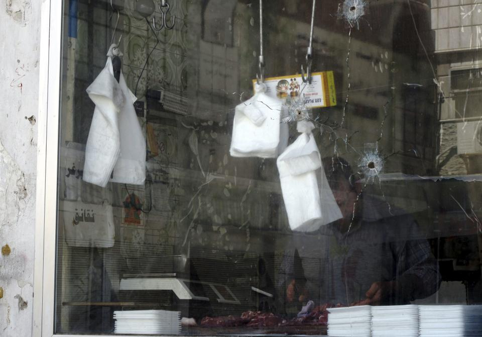 A butcher works in his shop damaged in recent fighting between the government troops and rebels in a Damascus neighborhood, Syria, Tuesday, April 3, 2012. A Syrian government official says troops have begun withdrawing from some cities and are returning to their bases. (AP Photo)