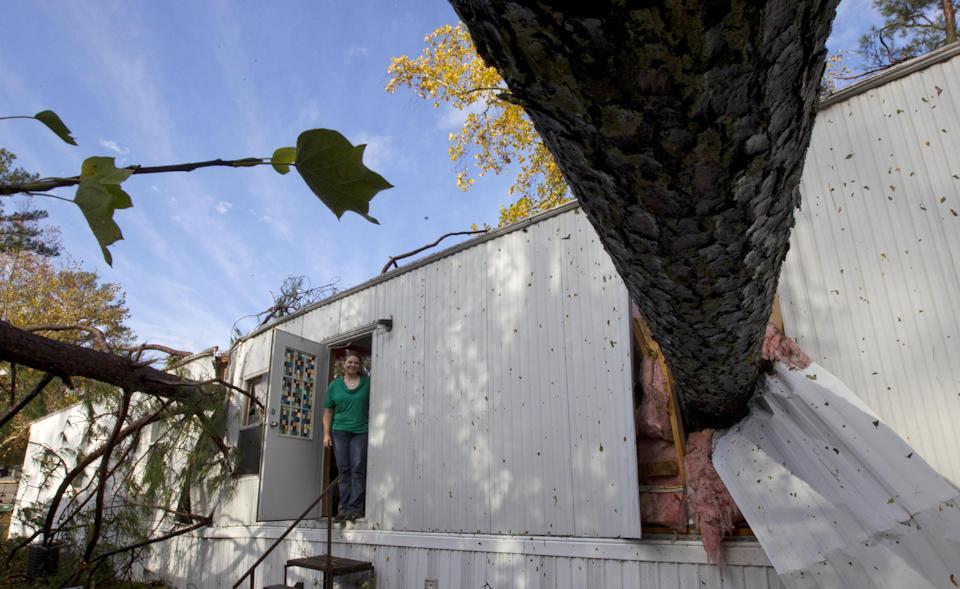Staci DeGeer looks out the door of her home in Auburn, Ala., Wednesday, Nov. 16, 2011.  Several trees were tossed into her kitchen and bedroom during a windstorm. A path of storms swept across the state leaving behind fallen trees and some heavy wind damage.  (AP Photo/Dave Martin)