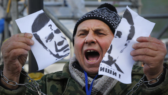 "A demonstrator holds a torn portrait of Ukrainian President Viktor Yanukovych and shouts ""Coward!"" during a rally in support of Ukraine's integration with the European Union in the center of Kiev, Ukraine, Friday, Nov. 29, 2013. Yanukovych said last week that he wouldn't sign the pact at an EU summit on Friday in Vilnius, Lithuania. The European Union extended its geopolitical reach eastward on Friday by sealing association agreements with Georgia and Moldova, but blamed Russia for missing out on a landmark deal with Ukraine. (AP Photo/Sergei Grits)"