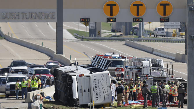 Emergency responders works the scene of  bush crash on the George Bush Turnpike Thursday, April 11, 2013, in Irving, Texas. The chartered bus overturned on the busy highway near Dallas on killing at least two people and injuring several others, authorities said. (AP Photo/LM Otero)