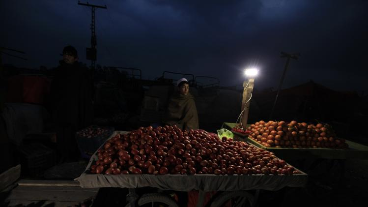 A vendor selling tomatoes on his push-cart waits for customers along a roadside in Islamabad
