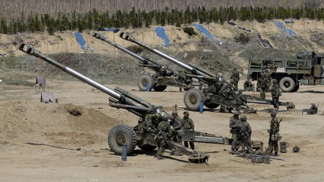 South Korean soldiers prepare 155 mm howitzers during their military exercise in the border city between two Koreas, Paju, north of Seoul, South Korea, Thursday, April 18, 2013. North Korea on Thursday demanded the withdrawal of U.N. sanctions and the end of U.S.-South Korea military drills as conditions for resuming talks meant to defuse tension on the Korean Peninsula. (AP Photo/Lee Jin-man)