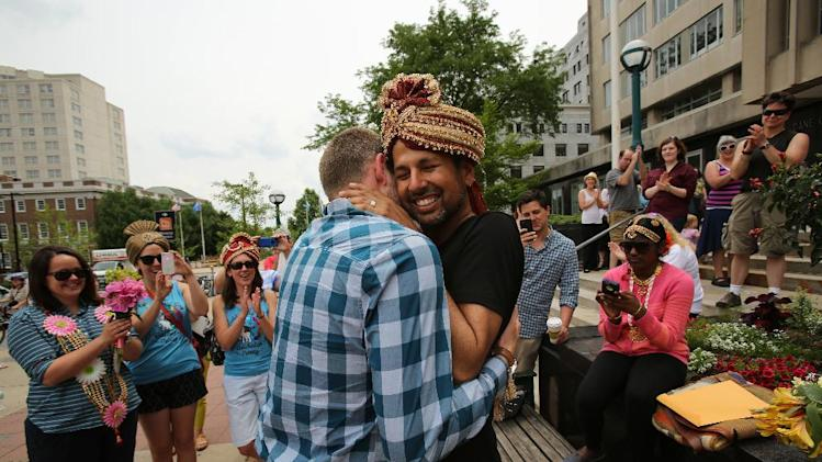Todd Kinsman, 28, left, and Ravi Manghnani, 37, hug after getting married by their friend, Michele Ritt, a Universal Life Minister, outside the City-County Building the day after the ban on same-sex marriage was struck down in Wisconsin, in Madison, Wis., Saturday, June 7, 2014. Kinsman and Manghnani, who have been together for seven years, had a ceremony a couple weeks ago and were just on their honeymoon in New York when they found out the ban was lifted and flew back home Saturday morning to get married in Madison. (AP Photo/Wisconsin State Journal, Amber Arnold)
