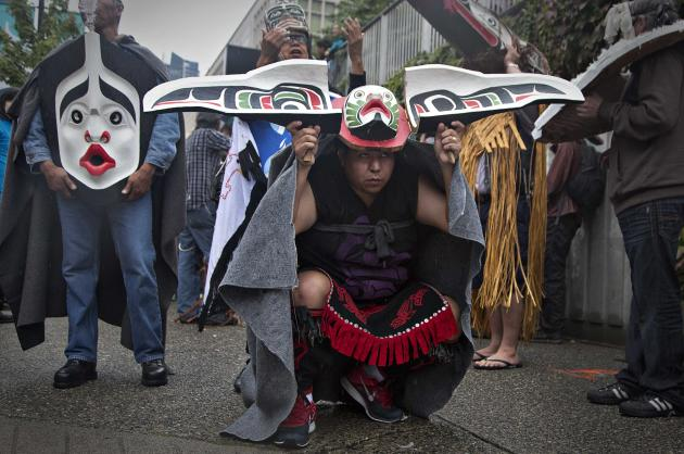 First Nations' participants whear traditional masks while waiting to take part in a Truth and Reconciliation march in Vancouver