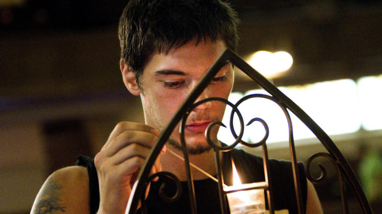 "Terry Willey, 24, lights a candle for the families and all involved with the Aurora shootings during services at the Grant Avenue United Methodist Church in Aurora, Colo. on Sunday, July 22, 2012, two days after a shooting rampage at a midnight showing of ""The Dark Knight Rises"" Batman movie. (AP Photo/Barry Gutierrez)"