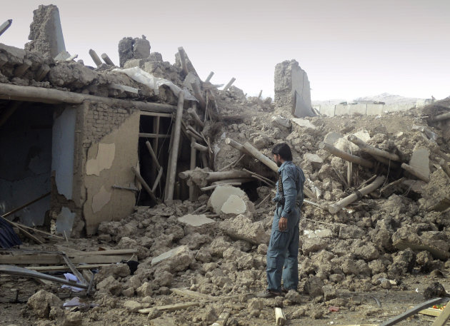 An Afghan police officer investigates the destruction outside Combat Outpost Sayed Abad in eastern Wardak province of Afghanistan on Sunday, Sept. 11, 2011. A powerful Taliban truck bomb that wounded 77 American soldiers and killed five Afghans outside a combat outpost served as a reminder on Sunday that 10 years after the Sept. 11 attacks, nearly 100,000 U.S. troops are still fighting a war that shows no signs of slowing down. (AP Photo/Mohammad Naser)