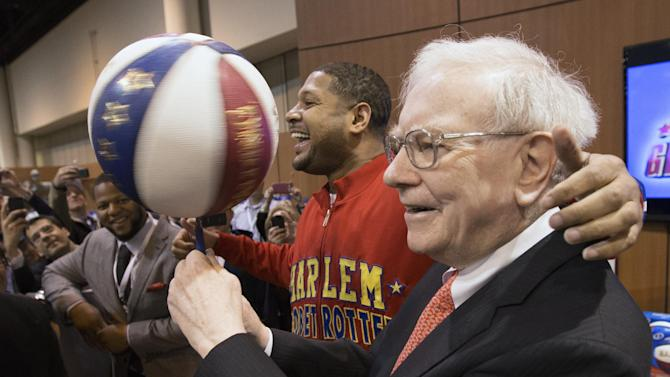 "Berkshire Hathaway Chairman and CEO Warren Buffett, right, is watched by Detroit Lions defensive tackle Ndamukong Suh, left, as he is assisted by Harlem Globetrotter Chris ""Handles"" Franklin in spinning a basketball in Omaha, Neb., Saturday, May 4, 2013, before holding the Berkshire Hathaway shareholders meeting. Tens of thousands attend Berkshire Hathaway shareholder meeting to hear Warren Buffett and Charlie Munger answer questions for more than six hours. No other annual meeting can rival Berkshire's, which is known for its size, the straight talk Buffett and Munger offer and the sales records shareholders set while buying Berkshire products. (AP Photo/Nati Harnik)"