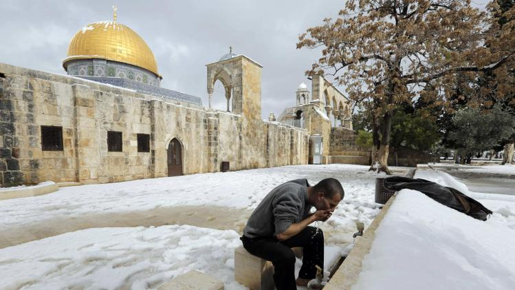 A Palestinian worshipper gets ready to pray his Friday prayer in front of the Dome of the Rock in the compound known to Muslims as Noble Sanctuary and to Jews as Temple Mount, in Jerusalem's Old City following a snowstorm