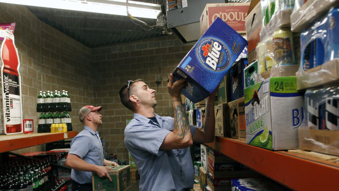 In this Monday, May 7, 2012 photo, Ryan Miller, right, and co-worker Jake Hotchkiss unload a delivery at a supermarket in Binghamton, N.Y. Miller, who served as a U.S. Army staff sergeant, knew that deserting his post was a serious crime. But he had a lot more on his mind and heart than than his job. While he was deployed as a cavalry scout in Afghanistan in 2003-2004, Miller's father died, his mother was diagnosed with cancer, and he was facing divorce. During his second tour, this time in Iraq, his best friend was killed by an roadside bomb. Some military justice insiders argue the way Miller's case was handled, which mirrors changes in civilian law for troubled veterans, should become more common as courts-martial deal with service members affected by battle-zone trauma. (AP Photo/Mike Groll)