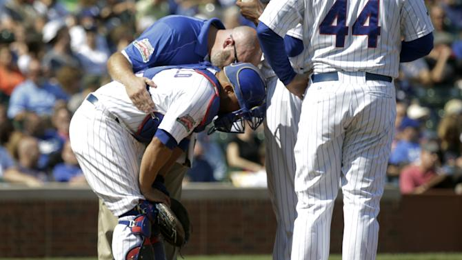 A member of the Chicago Cubs medical staff attends to catcher Welington Castillo during the first inning of a baseball game against the Los Angeles Dodgers, Friday, Sept. 19, 2014, in Chicago. (AP Photo/Charles Rex Arbogast)