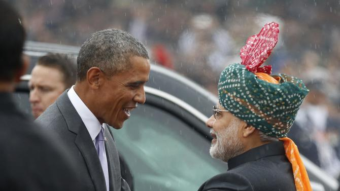 U.S. President Obama shakes hands with India's Prime Minister Modi in the pouring rain as he arrives to attend the Republic Day parade in New Delhi