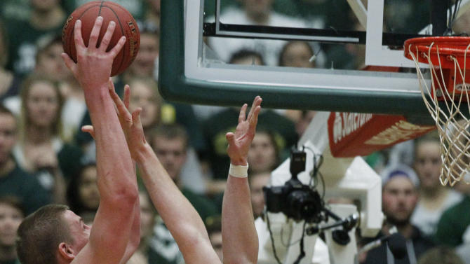 Colorado State center Colton Iverson, left, goes up for a shot over New Mexico center Alex Kirk in the second half of New Mexico's 91-82 victory in an NCAA basketball game in Fort Collins, Colo., on Saturday, Feb. 23, 2013. (AP Photo/David Zalubowski)