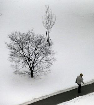 A person walks by a snow covered area outside of the Somerset County Superior Court, Tuesday, Dec. 17, 2013, in Somerville, N.J. A mix of snow and rain covered the northern New Jersey region with a storm that moved in early in the day. (AP Photo/Julio Cortez)