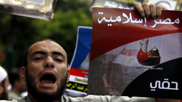 "FILE - In this Friday, Sept. 23, 2011 file photo, an Egyptian man chants slogans and holds a poster that reads, in Arabic, ""Islamic Egypt,"" during a demonstration held by a Salafi group to protest the emergency law, in Tahrir Square in Cairo, Egypt. Under Mubarak, there were no mass killings along the lines of South African or some Latin American dictatorships in the 1980s. But tens of thousands of political prisoners were detained under emergency laws that expired last week after 31 years in force. Torture was systematic, and often extreme, and corruption was completely endemic. (AP Photo/Khalil Hamra, File)"