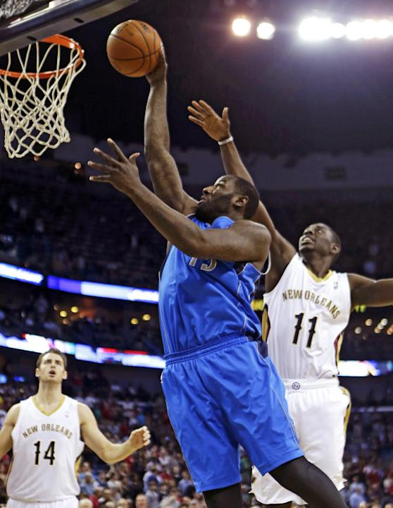 Dallas Mavericks center DeJuan Blair (45) drives to the basket between New Orleans Pelicans point guard Jrue Holiday (11) and center Jason Smith (14) in the first half of an NBA basketball game in New
