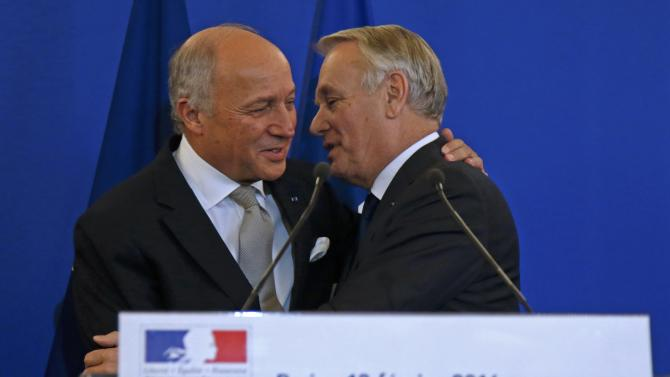 Outgoing French Foreign Minister Laurent Fabius embraces newly-appointed Foreign Minister Jean-Marc Ayrault during the official handover ceremony at the Quai d'Orsay in Paris
