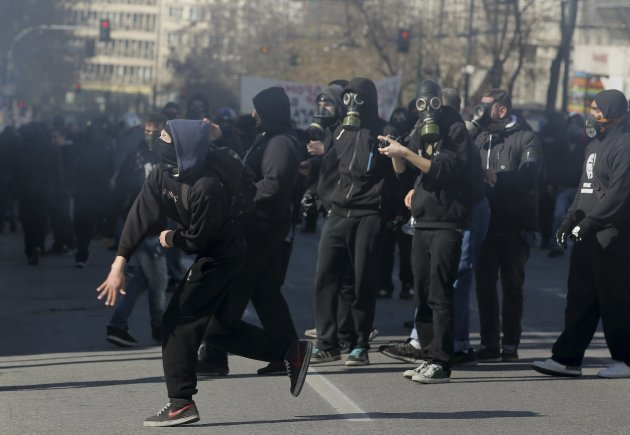 Masked protesters throw rocks at policemen following an anti-austerity march during a 24-hour strike in Athens