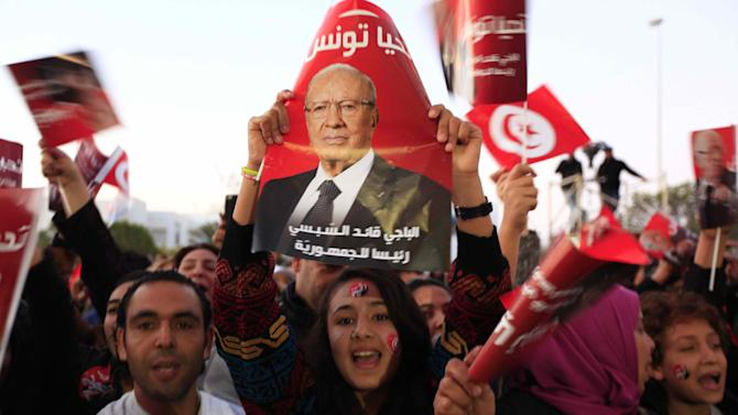 Nidaa Tounes party supporters wave flags and shout slogans as they celebrate in Tunis