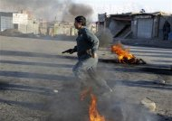 An Afghan policeman runs for cover during clashes with protesters in Kabul February 24, 2012. REUTERS/Omar Sobhani