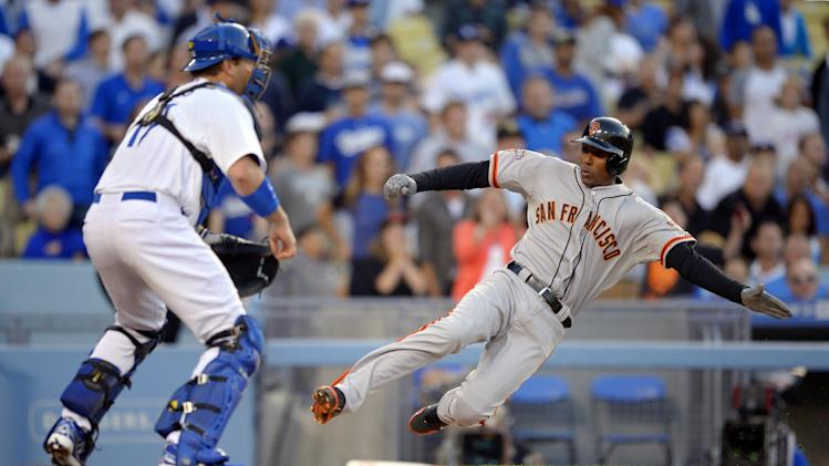 San Francisco Giants' Joaquin Arias, right, scores on a double by Andres Torres as Los Angeles Dodgers catcher A.J. Ellis takes a late throw during the second inning of their baseball game, Monday, June 24, 2013, in Los Angeles. (AP Photo/Mark J. Terrill)
