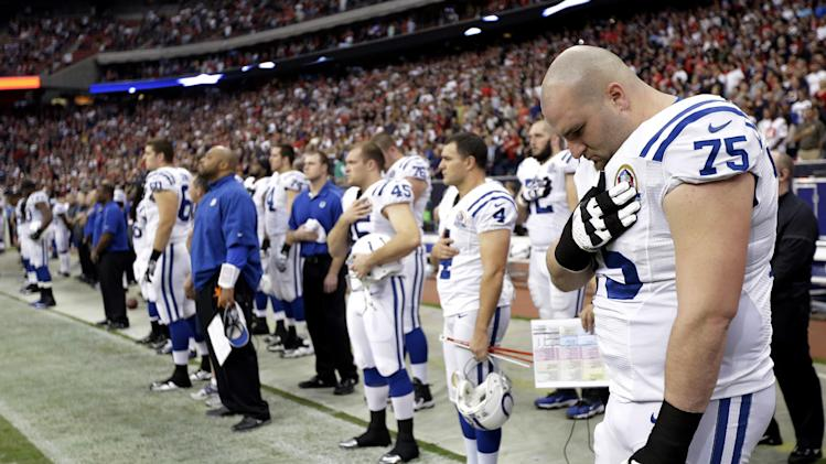 Indianapolis Colts guard Mike McGlynn (75) bows his head during a moment of silence for the victims of the Sandy Hook Elementary School shootings before an NFL football game against the Houston Texans Sunday, Dec. 16, 2012, in Houston.    A gunman walked into Sandy Hook Elementary School in Newtown, Conn. Friday and opened fire, killing 26 people, including 20 children. (AP Photo/Eric Gay)