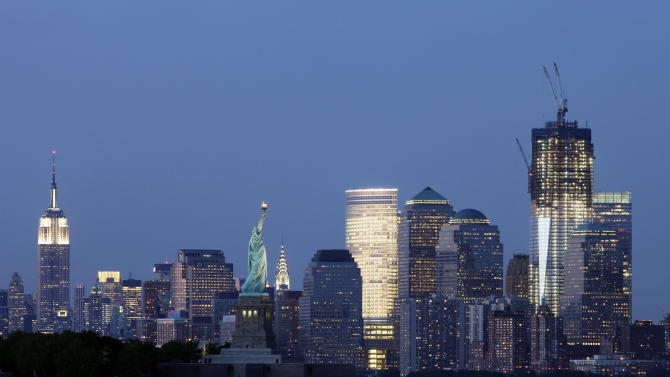 The Empire State Building, left, the Statue of Liberty, center, and One World Trade Center, right, frame the New York skyline, on Tuesday, Aug. 23, 2011. (AP Photo/Mark Lennihan)
