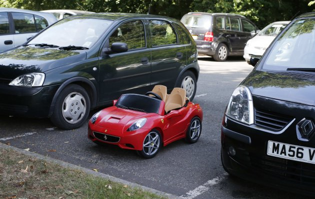 A child's toy Ferrari is parked between two hatchbacks at the Hale Barns Cricket Club in Altrincham, Cheshire, northern England