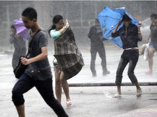 People brave strong winds and rain on a street as a typhoon hit Haikou in south China's Hainan province, Thursday, Sept. 29, 2011. The powerful typhoon slammed into southern China on Thursday after skirting Hong Kong and bringing death and widespread flooding to the Philippines earlier this week (AP Photo) CHINA OUT