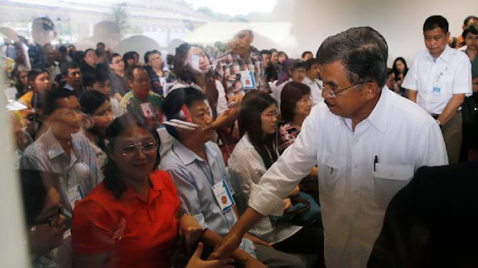 Indonesia's vice-president Kalla shakes hands with family members of passengers onboard AirAsia flight QZ8501 in Surabaya
