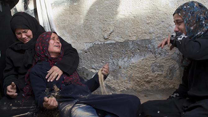 Palestinian women cry during the funeral of Tahrer Salman and Mohammed Salman in Beit Lahia, north Gaza, Friday, Nov. 16, 2012.  According to relatives, the two members of the Salman family were killed after an Israeli airstrike hit the yard of their house. At least 22 Palestinians, including 12 militants and six children, as well as three Israelis have been killed in three days of fierce exchanges between the Israeli military and Gaza militants. (AP Photo/Bernat Armangue)