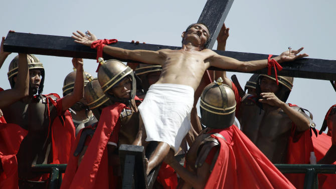 A Filipino penitent who is nailed to a wooden cross is raised by actors portraying Roman soldiers during Good Friday rituals on March 29, 2013 at Cutud, Pampanga province, northern Philippines. Several Filipino devotees had themselves nailed to crosses Friday to remember Jesus Christ's suffering and death, an annual rite rejected by church leaders in this predominantly Roman Catholic country. (AP Photo/Aaron Favila)