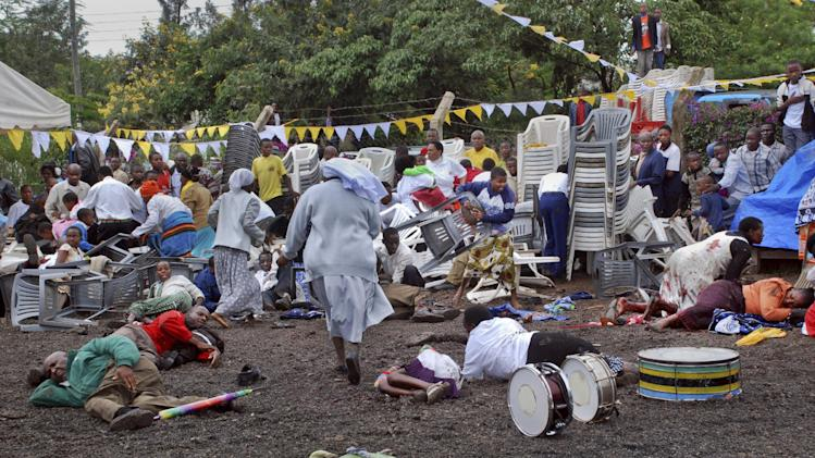 Wounded churchgoers lie on the ground as Roman Catholic nuns run for cover after a blast at the St. Joseph Mfanyakazi Roman Catholic Church in Arusha, Tanzania Sunday, May 5, 2013. A Tanzanian police official says a woman died and over 40 people were seriously injured when a bomb exploded in the Roman Catholic Church in northern Tanzania, with eyewitnesses reporting that the bomb was thrown from a motorcycle. (AP Photo)