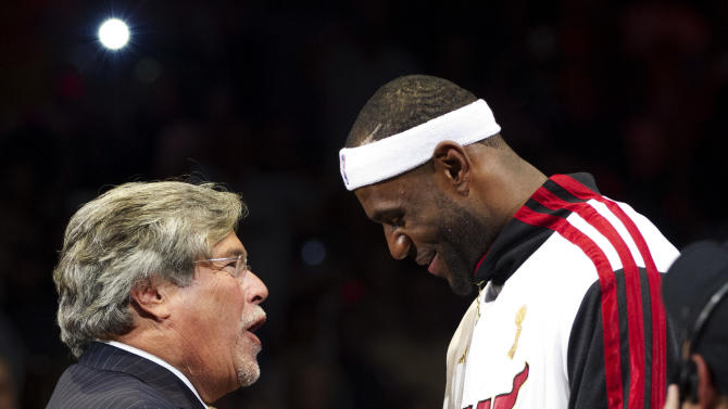Miami Heat owner Mickey Arison, left, presents LeBron James with his 2012 NBA Finals championship ring during a ceremony before a basketball game against the Boston Celtics, Tuesday, Oct. 30, 2012, in Miami. (AP Photo/J Pat Carter)