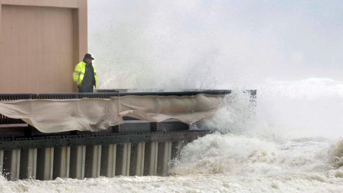 An unidentified Okaloosa County Deputy Sheriff stands next to the Jetty East condominium in Destin, Fla., Tuesday, Aug. 28, 2012 as a wave crashes over the buildings boardwalk. Although Isaac is expected to make landfall in Louisiana, the storm still pounded shorelines along Northwest Florida as it moved through the Gulf of Mexico. (AP Photo/Northwest Florida Daily News, Devon Ravine)