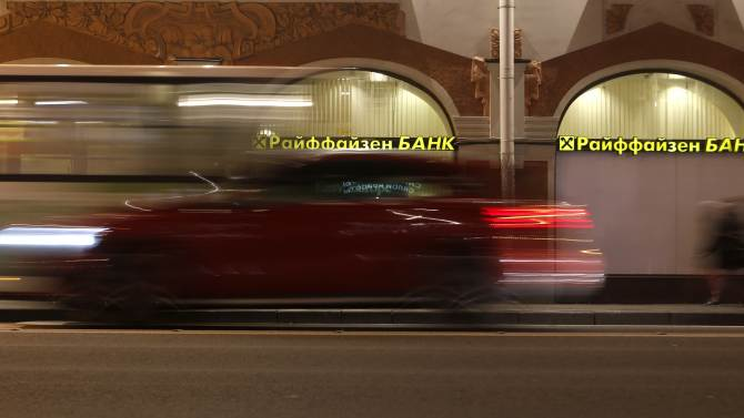 A car drives past a branch office of Raiffeisen Bank in St. Petersburg