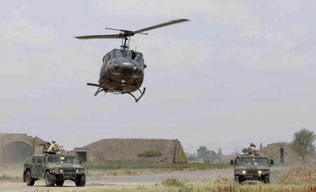 """Georgian medevac helicopter flies over US marine Humvees during a joint military exercise with NATO members, called """"Agile Spirit 2015"""" at the Vaziani military base outside Tbilisi"""