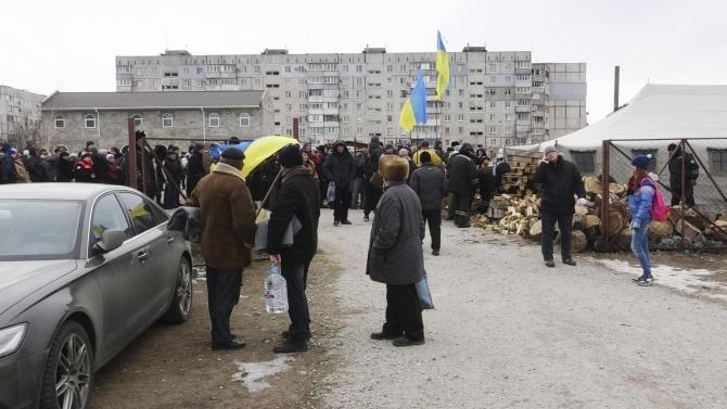 People queue to receive aid after the city was hit by shelling on Saturday in Mariupol, eastern Ukraine