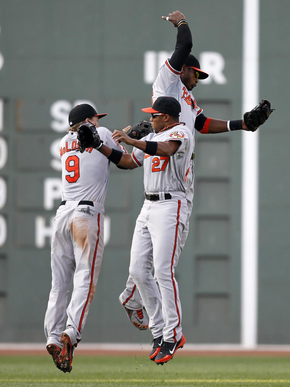 Baltimore Orioles' Nate McLouth (9), Endy Chavez (27) and Adam Jones, top, celebrate after defeating the Boston Red Sox 9-6 in the 12th inning of a baseball game in Boston, Saturday, Sept. 22, 2012. (AP Photo/Michael Dwyer)