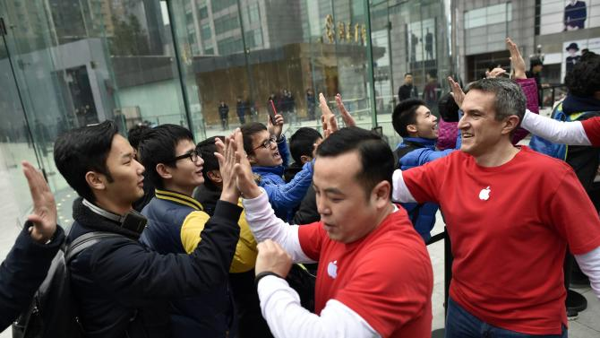 Employees greet customers queuing for the opening of a new Apple Store in Chongqing municipality