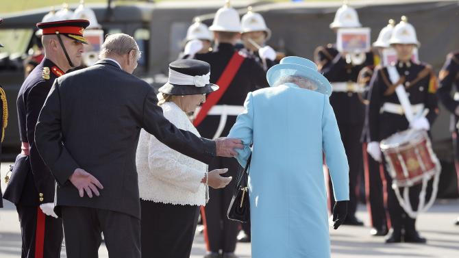 Britain's Queen Elizabeth is helped by the Prince Philip, the Duke of Edinburgh, before inspecting a guard of honour with Malta's President Marie Louise Coleiro Preca at Luqa airport, near Valletta