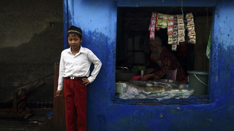 Boy poses with a dart in his hand near a sundry shop close to his school at Cilincing in Jakarta