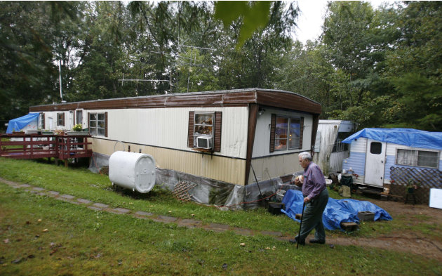 In this Sept. 15, 2011 photo, Bill Ricker, 74, walks to his trailer in Hartford, Maine. Ricker, who has two college degrees, has worked as an electronics repairman, a pastor and a TV cameraman. He and