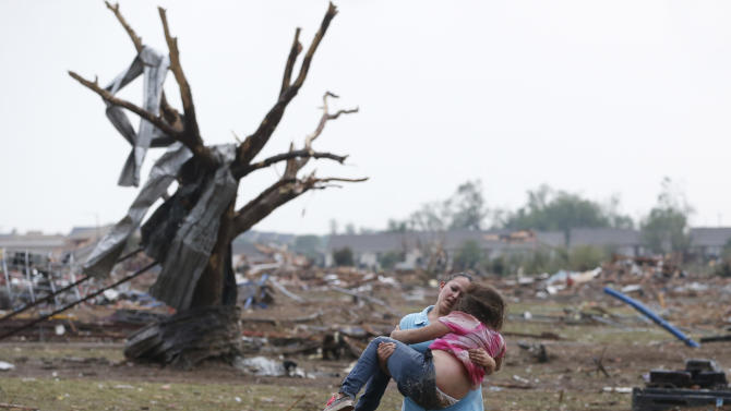 FILE - In this May 20, 2013 file photo, LaTisha Garcia carries her 8-year-old daughter, Jazmin Rodriguez near Plaza Towers Elementary School after a massive tornado carved its way through Moore, Okla., leaving little of the school and neighborhood. This picture, published on hundreds of front pages around the world, has become one of the enduring images from the storm. (AP Photo/Sue Ogrocki,File)