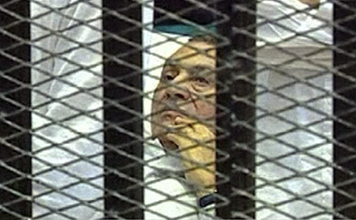 FILE - This Aug. 3, 2011 file image taken from Egyptian State Television shows Hosni Mubarak, 83, lying on a hospital bed inside a cage of mesh and iron bars in a Cairo courtroom as his historic trial begins on charges of corruption and complicity in the killing of protesters during the uprising that ousted him. Relatives of protesters killed during Egypt's uprising scuffled with police and tried to force their way into a Cairo courtroom Monday, Sept. 5, 2011 demanding to be allowed to attend the latest session in the trial of ousted President Hosni Mubarak. Live TV broadcasts of the landmark trial have been halted by a judges' order, and family members massed outside the courtroom were angered they could not witness the prosecution of the former leader charged with complicity in their loved ones' deaths.(AP Photo/Egyptian State TV, File)  EGYPT OUT
