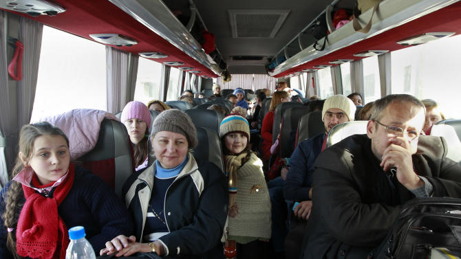 A group of Russian citizens ride a bus shortly after crossing the border from Syria into Lebanon at the Masnaa border crossing Tuesday, Lebanon, Jan. 22, 2013. Some 80 Russian citizens crossed into Lebanon as Moscow began evacuating some of the tens of thousands of Russians who live in Syria. (AP Photo/Bilal Hussein)