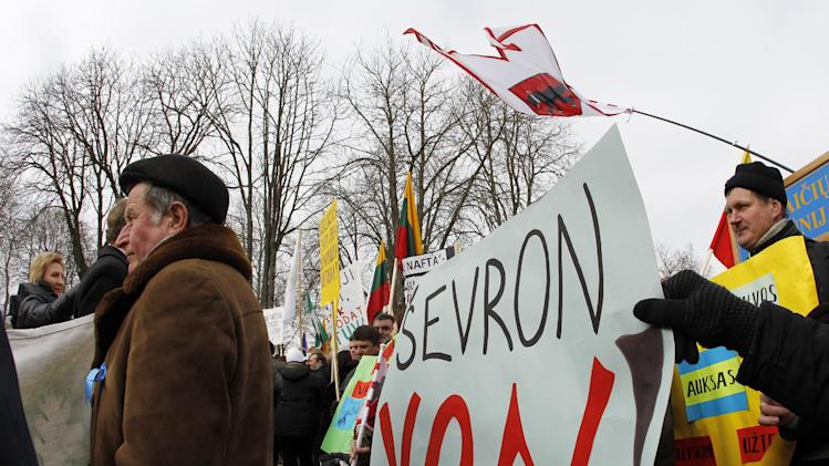 Lithuanians gather for an anti-American demonstration rally at the President  palace in Vilnius, Lithuania, Tuesday, Feb. 26, 2013. Protesters oppose government plans to explore shale gas fields in the western part of the country.  Poster at right reads 'Chevron Out.' (AP Photo/Mindaugas Kulbis)