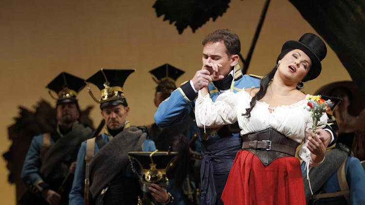 "In this Sept. 20, 2012 photo, Mariusz Kwiecien performs as sergeant Belcore alongside Anna Netrebko performing as Adina during the final dress rehearsal of Gaetano Donizetti's ""L'Elisir d'Amore"" at the Metropolitan Opera in New York. That most endearing of all comedies, Donizetti's ""L'Elisir d'Amore,"" opened the Metropolitan Opera season on Monday, Sept. 24 in a modest new production made memorable by an outstanding cast. (AP Photo/Mary Altaffer)"