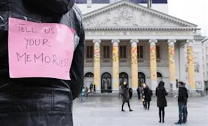 A woman shows a sign, near columns of the Munt (Monnaie) Opera decorated with Post-its, in Brussels December 16, 2012. REUTERS/Sebastien Pirlet